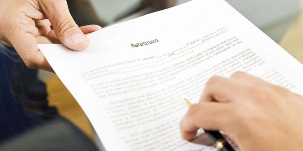 a picture of a person handing a agreement paper